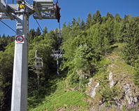Chair lift up wooded mountains in summer Stock Photos