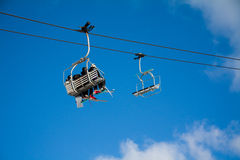 Chair lifts with sky and clouds. Two chairlift seats with people seated in one and the other empty. With blue empty sky and some cloud on the right Stock Photo