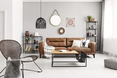 Chair near table in grey apartment interior with mirror and leather sofa. Real photo. Chair near table in grey apartment interior with mirror and poster on the stock photography