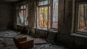 Chair opposite the window in the room of an old ruined abandoned house in Pripyat in Ukraine royalty free stock photo