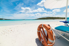 Chair and parasol by the sea. Beach chair and parasol by the sea under a cloudy sky stock image