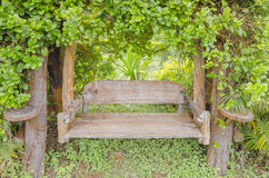 Chair in the park. Wood chairs have a shrubbery cover in the garden for relaxation on holiday Stock Photos