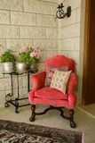 Chair and plant in corner. Colorful Arabian chair with handmade silk pillows and a plant stand in an interior corner Royalty Free Stock Image