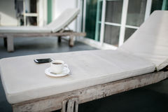Coffee and MobilePhone on a Chair with pool in resort Stock Image