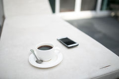 Coffee and MobilePhone on a Chair with pool in resort Royalty Free Stock Photo