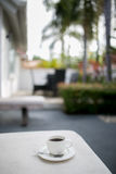 Coffee and MobilePhone on a Chair with pool in resort Royalty Free Stock Photography