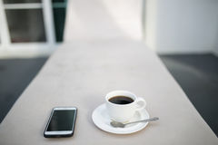 Coffee and MobilePhone on a Chair with pool in resort Stock Photo