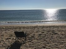 Morning on the beach in front of the water. A chair put on the beach where you can sit in front of the sea and just chilling out stock photos