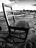 A Chair Rests on the Sunny Shores of Lake Erie. The beautiful beaches of Cleveland, Ohio are a bastion of fresh water Royalty Free Stock Image