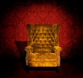Chair in a room. A grungy gold velvet chair in a dark room with red Victorian wallpaper Stock Images