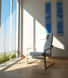 Chair on a room corner, besides a large window in the sun. Royalty Free Stock Photography