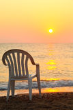 Chair is on seashore. beautiful orange sunset Stock Photography