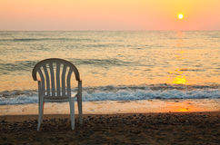 Chair is on seashore. beautiful orange sunset Royalty Free Stock Image