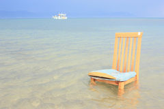 Chair and ship in the distance Royalty Free Stock Image