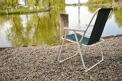 Chair at shore of lake, perfect place for relaxing and meditat Royalty Free Stock Photo