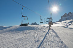 Chair ski lift over snow. Chair ski lift driving over ski slope in the Dolomiti. Sun in the front. Skiers. Blue sky Royalty Free Stock Image