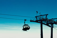 Chair ski lift with skiers going up Royalty Free Stock Photo
