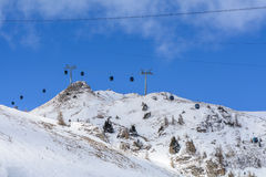 Chair ski lift with skiers over blue sky.  Panorama of snow moun Royalty Free Stock Photo