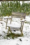 Chair in the snowy vegetable garden. A snow covered chair near a vegetable garden on a wintry day royalty free stock images