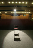 Chair on stage. Red chair on brown stage lighted with a spotlight, empty seats in background Royalty Free Stock Images