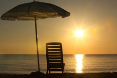 Chair stands on beach under opened umbrella Royalty Free Stock Image
