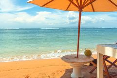 A chair and a stone table on the yellow beach under a parasol,. Relaxing with a coconut-drink. Sanur, Bali, April 21, 2018 Stock Photo