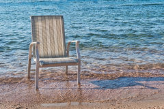 A chair stood in the sea water near the coast stock images