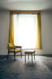 Chair and stool by the window Stock Image