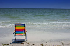 Chair and Surf. Vivid colored beach chair on Florida's Gulf Coast. Madeira Beach Florida royalty free stock images