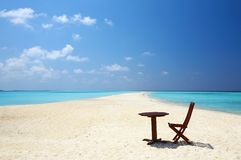 Chair and table are on the beach. Chair and table are on the coral sandy beach, Maldives royalty free stock photography