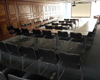 Classroom with chairs black color and slide projector. Chair, table, education, nobody, school, design, work, seat, seating, row, equipment, indoor, nobody stock photos