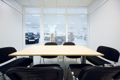 Chair and table in room and new cars in office Stock Image