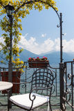 Chair on a terrace overlooking peaceful lake and mountains in af. Idyllic scene of a chair on a terrace overlooking lake Como in afternoon sunlight under a blue Stock Photography