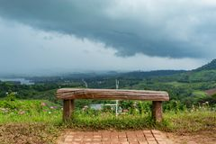 Chair on top of the mountain and the sky raining. stock photography