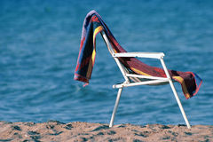 Chair and towel. Sea, sand, sun and one chair Royalty Free Stock Photos