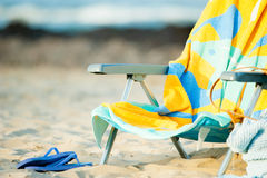 Chair with towel and Sandals on the beach Stock Photos