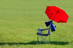 Chair and Umbrella. A foldable chair and a red umbrella on the lawn Stock Photography