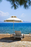 Chair and umbrella at greek beach Royalty Free Stock Photo