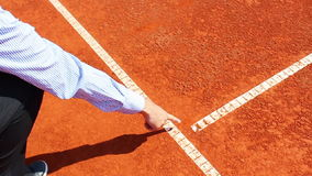 Chair umpire checking mark on clay tennis court stock video footage