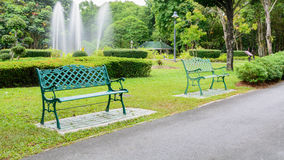 Chair beside walkway in park Stock Photos