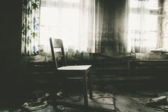Chair by the window. An old rustic chair at a window Royalty Free Stock Images