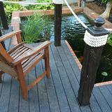 Rest place near pond in private garden. Chair on wooden deck near morden pond in private garden. Summertime. Rest Royalty Free Stock Photo