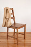 Chair on wooden floor with clothing over its back Royalty Free Stock Photo