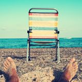 Chair and young man on the beach, filtered. Closeup of the feet of a young caucasian man relaxing and a striped folding chair on the beach, with a filter effect Royalty Free Stock Images