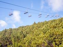 Chairlift σύστημα μεταφοράς πέρα από τα πράσινα δέντρα πεύκων Στοκ εικόνα με δικαίωμα ελεύθερης χρήσης