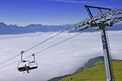 Chairlift above clouds Royalty Free Stock Image