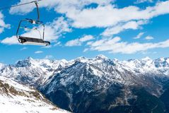 Chairlift against snowy Alpine mountains. Austria Stock Photos