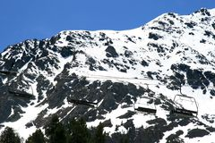 Chairlift against white mountains. In springtime the chairlift in the mountains of Andorra, the Pyrenees, are hanging in rest. Snow is still covering the high Royalty Free Stock Image
