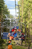 Young couple sitting on chairlift forest Stock Image