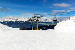 Chairlift in the Italian Alps. Chair lift in snowy mountains at nice sunny day. stock image